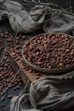 Coffee beans in a plate on a wooden stand. Low key photography close up. 写真素材