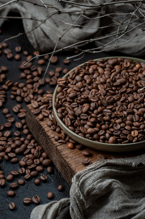 Freshly roasted coffee beans on a dark table. Low key photography close up.