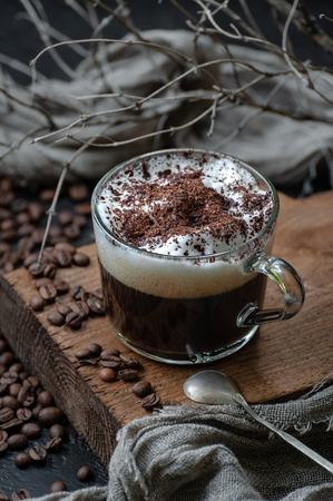 Coffee americano with milk foam and chocolate on a wooden board closeup. Low key photography. 写真素材