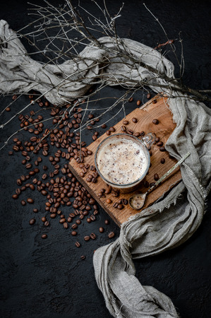 Cappuccino coffee with milk foam and chocolate on a wooden board with additional accessories. Low key photography.