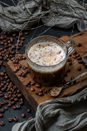 Coffee with milk foam on a wooden board and a scattering of coffee beans. Low key photography.