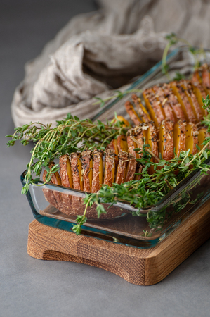 Baked potatoes with thyme in a glass in a rustic style. 写真素材