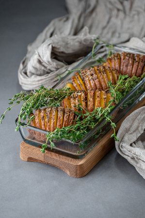 Baked potatoes with thyme in a glass container on a gray stone table. 写真素材