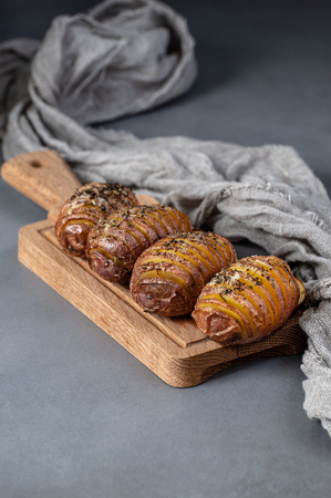 Whole baked potatoes with thyme on a wooden board on a gray stone table. 写真素材