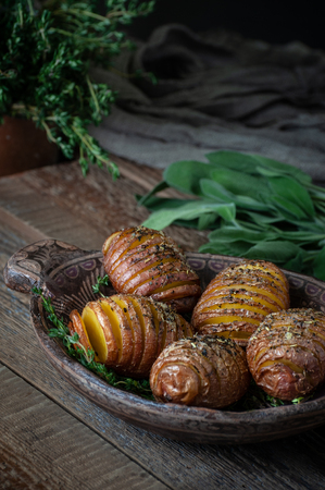 Whole baked potatoes with thyme in a wooden plate on an old rustic table.