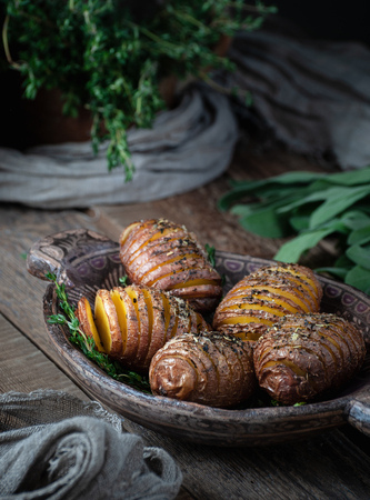 Baked potatoes in a wooden plate in a rustic style. Food photography in a low key.