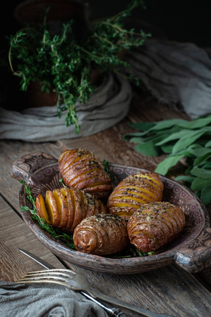 Whole baked potatoes with thyme in a wooden plate on an old rustic table. Shooting in low key.