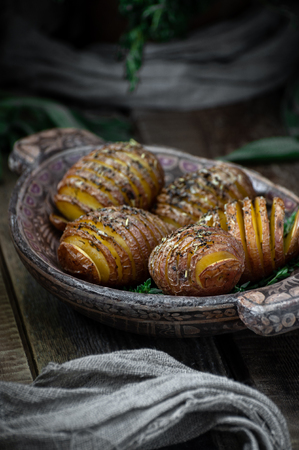 Baked whole potatoes with herbs and spices. Food photography in a rustic style.