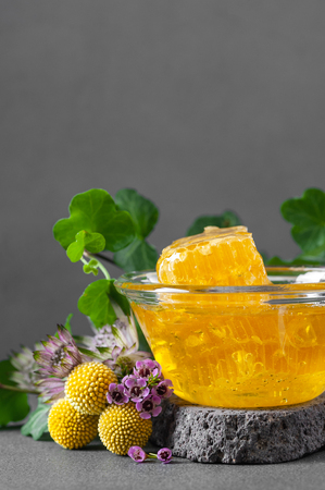 Honeycombs and floral honey with wildflowers. Vertical photo with negative space.