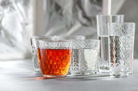 Glasses with water and alcoholic drink on a gray stone table. Shooting with strong light. 写真素材
