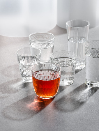 Glasses with water and a drink on a gray stone table. Shooting with hard light. 写真素材
