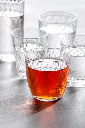 Glass glasses with water and drinks on a gray stone background. 写真素材