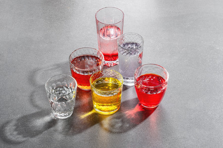 Colored drinks in glass cups on a gray stone table.