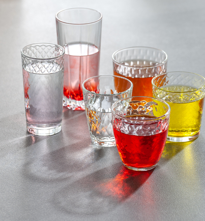 Colored soft drinks in glass faceted glasses on a gray table. Photo with a gradient background.