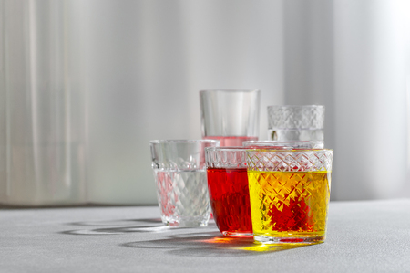 Colored drinks in glass cups on a gray background. 写真素材