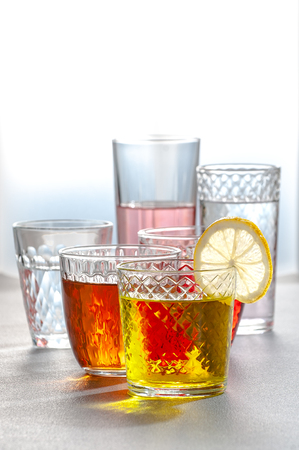 Various lemonades in glass faceted glasses on a gray table. Photo with a gradient background.