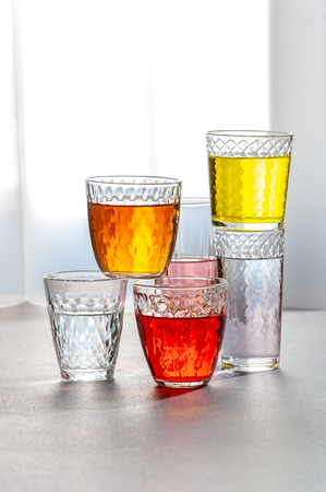 Various lemonades in glass faceted glasses on a gray table. 写真素材