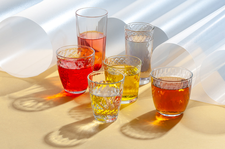Colored drinks in glass cups on a yellow background with additional elements.