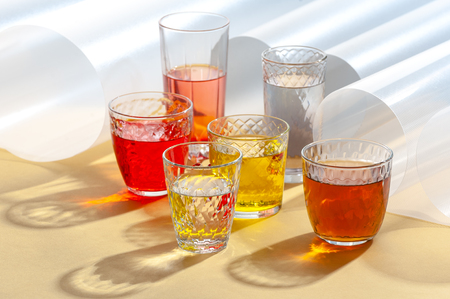 Multicolored soft drinks in glass cut glasses on a yellow table.