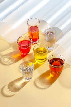 Glass cups with multi-colored cold drinks on a yellow background. Shooting with hard light.
