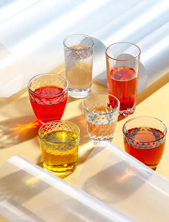 Glass cups with colorful cold drinks on a yellow background with additional elements. Shooting with hard light. 写真素材