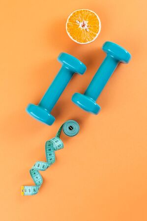 Dumbbells, a centimeter and half an orange on a light orange background.