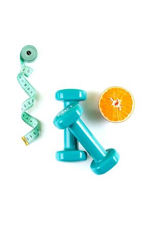 Dumbbells, a centimeter and half an orange on a pure white background.  Stockfoto