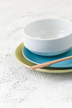 Plates, bowl and wooden spoon on a light gray textural background.  Stockfoto