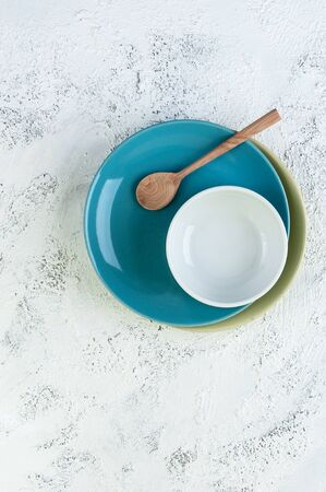 Two plates, a bowl and a wooden spoon on a light gray textural background. Фото со стока