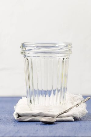 An empty facetted jar on a tissue napkin on a blue table.