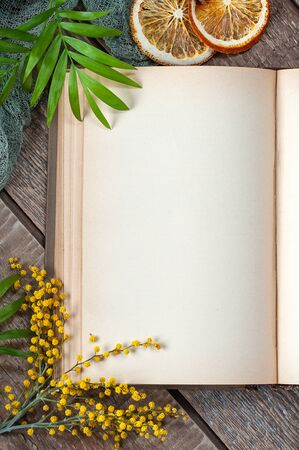 Half open book with blank pages on an old wooden table in spring design. Photography for your design.