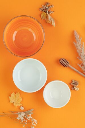 Three empty bowls of different sizes on a bright orange background.