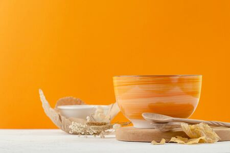 Orange salad bowl on a stand and wooden spoons on a bright orange background. Autumn decoration.