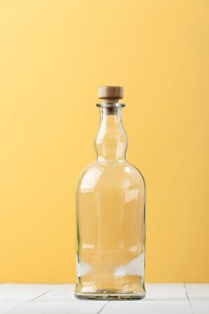 An empty relief glass bottle on a light white-yellow background.  Stockfoto