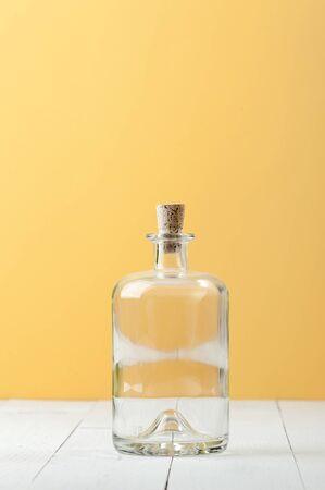 Empty glass bottle for rum on a light white-yellow background. 版權商用圖片