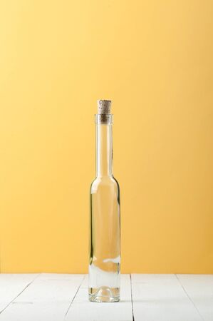 A narrow long glass bottle on a light white and yellow background.