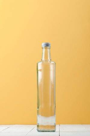 Straight long glass bottle on a light white-yellow background.  Stockfoto