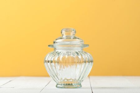 Glass jar with a lid on a white table near the yellow wall.  Stockfoto