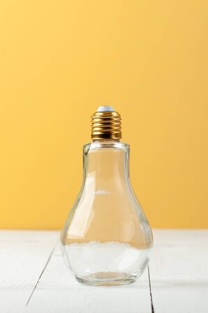 A bottle in the form of an incandescent lamp with a curved cover on a white-and-yellow background.