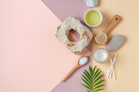 Accessories, olive oil and body care cosmetics on a light pastel background.