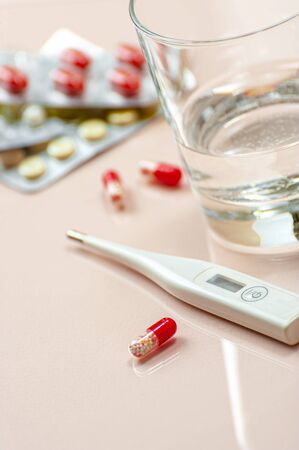 Antibiotic tablet, a glass of water and a thermometer on a beige pastel background. 版權商用圖片