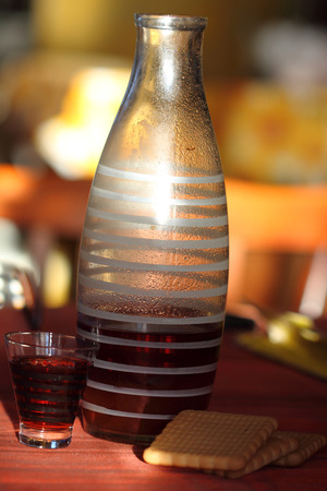 guelderrose: old kind house liqueur from a guelder-rose in a striped glass Stock Photo