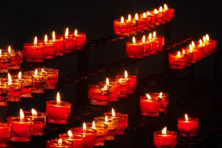 small burning church candles in red glass candleholders photographed diagonally on the chandelier Banco de Imagens