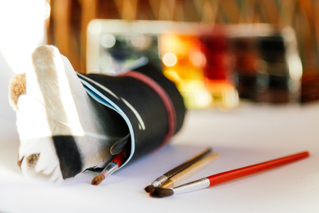 brushes, paints and drawing paper on a white background, conceptual for artists and designers