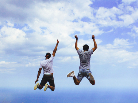 Two young men jump up with their hands high against the sky