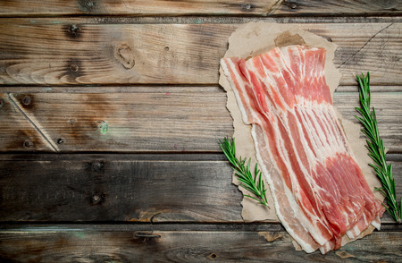 Raw bacon on paper. On a wooden background.