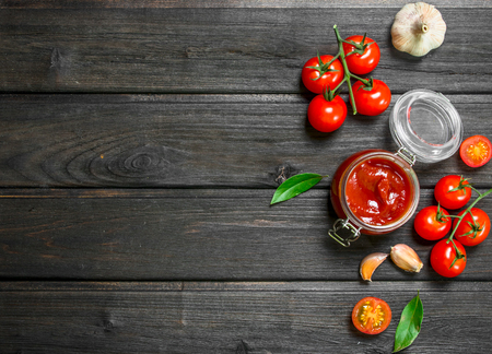 Tomato sauce in a glass jar with Bay leaf and cherry. On wooden background