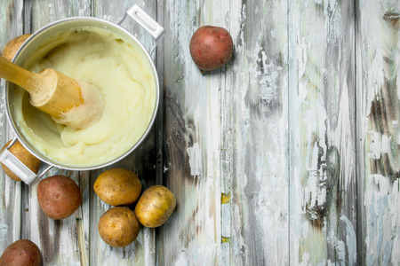 Mashed potatoes in a pot . On a rustic background.
