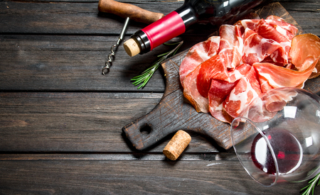 Spanish ham with a glass of red wine. On a wooden background. Фото со стока