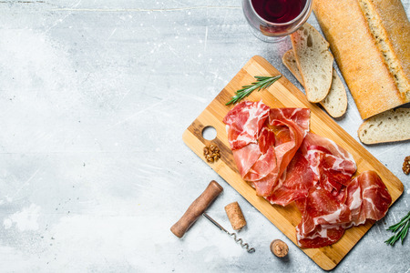 Traditional Spanish ham with ciabatta and red wine. On a rustic background. Standard-Bild